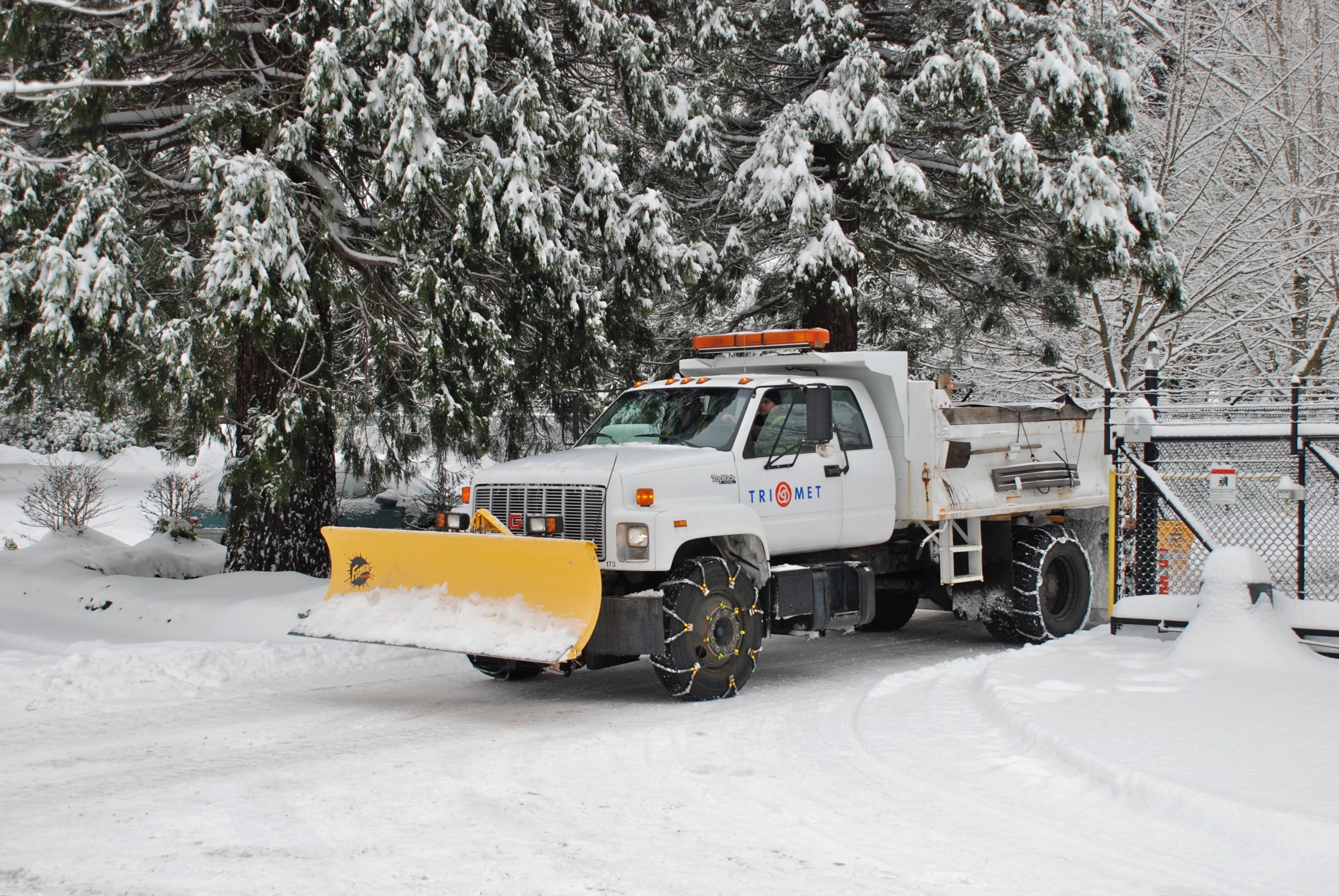 Small dump truck equipped with a snow plow on the front and with tire chains of two different types. TriMet (Portland, Oregon, transit system), Dec. 2008.